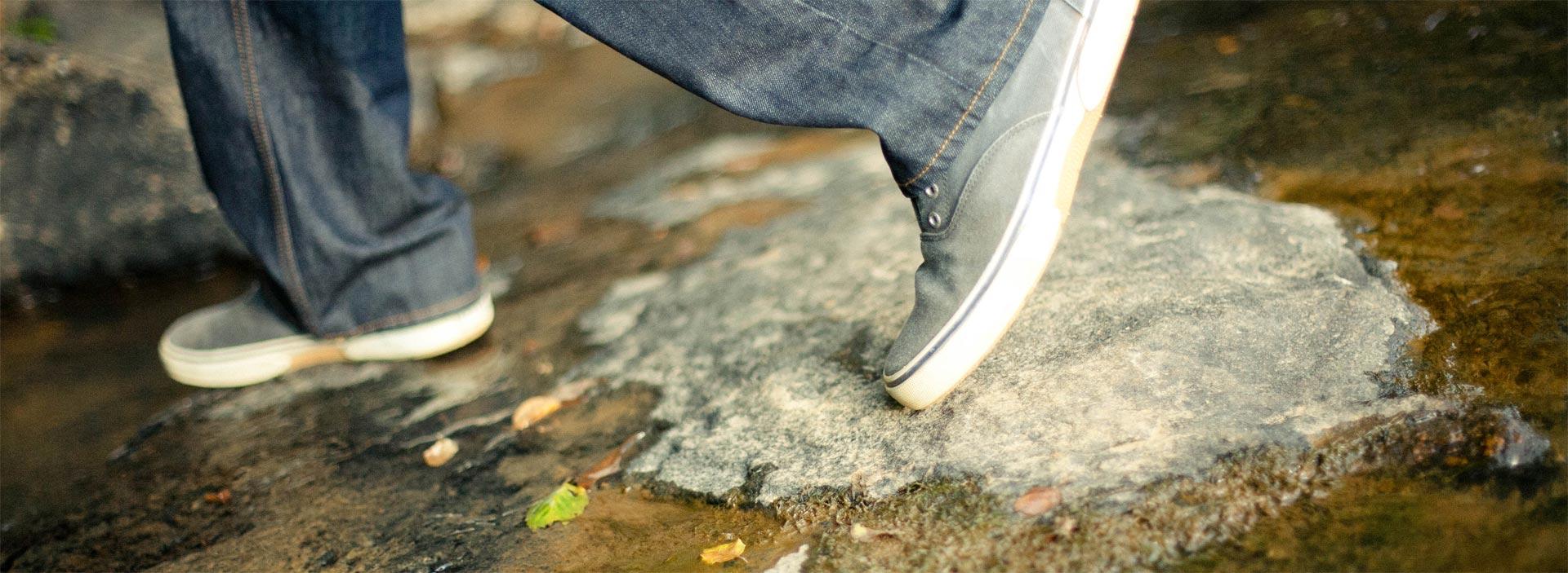 Shoes walking through puddle